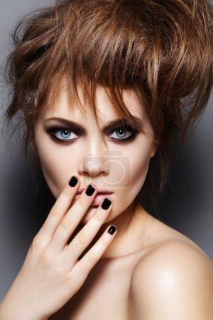 Photo pour Mannequin avec les cheveux ébouriffés, maquillage, manucure. Portrait de mode jeune femme avec une coiffure de punk rock, sombre maquillage, vernis à ongles noir - image libre de droit