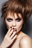 Modelka s rozcuchanými vlasy, make-up, manikúra. módní portrét