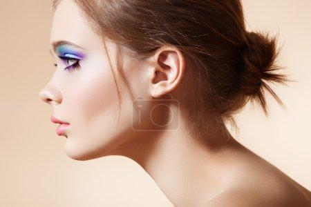 Photo pour Belle vue de profil de visage de modèle féminin avec maquillage de mode lumineux et coiffure simple sensualité sur fond beige . - image libre de droit