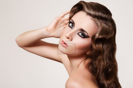 Beautiful woman model with shiny curly hairstyle and dark smoky eyes