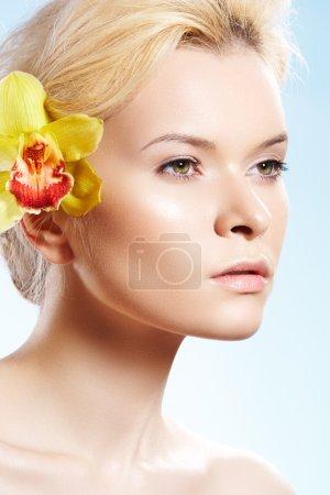 Foto de Salud, spa, wellness, belleza y cuidado de la piel. primer retrato de mujer hermosa con maquillaje natural, piel brillante perfecta, flor amarilla. - Imagen libre de derechos