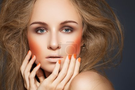 High fashion look. Woman model with fashionable makeup, bright orange blush