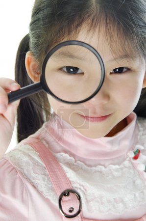 A little girl peers at the camera through a magnif...