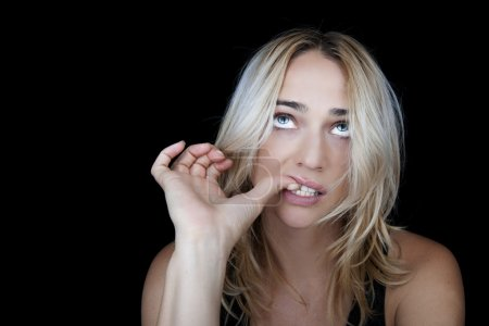 Beautiful blonde woman biting her nails.