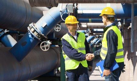 Photo pour Deux ingénieurs réunis à l'extérieur à la tuyauterie d'une facilité de nettoyage les eaux usées industrielles - image libre de droit