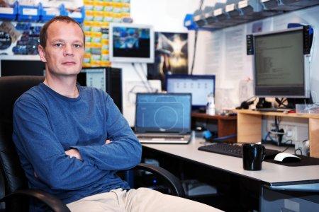 Photo pour Portrait d'un technicien en informatique cherche poupe dans un atelier de réparation en désordre, avec différents ordinateurs, écrans et composants matériels en arrière-plan - image libre de droit