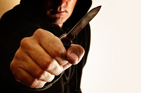 Photo for Crouching robber with small knife - Royalty Free Image