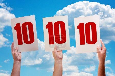 Photo pour Livre blanc avec numéro dix à male mains sur fond de ciel bleu - image libre de droit