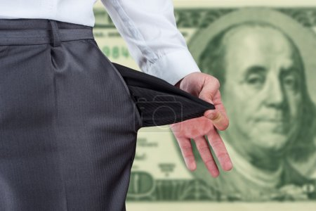Photo for Businessman pulling empty pocket out of pants against dollar banknote - Royalty Free Image