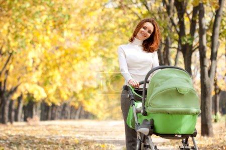 Photo pour Heureuse jeune maman avec bébé en buggy marche dans le parc automne - image libre de droit