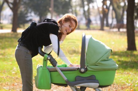 Young mother carrying baby in autumn park