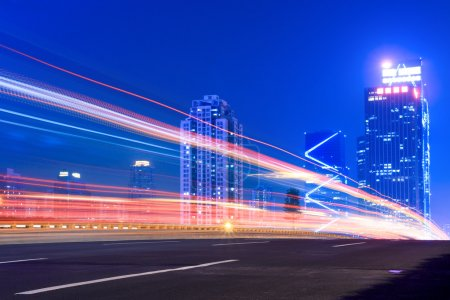 Photo for Light trails on the highway with modern building background at night - Royalty Free Image