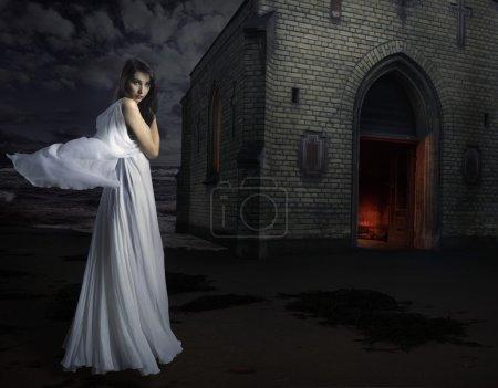 Photo pour Femme en robe blanche devant une église - image libre de droit