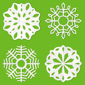 Set of white paper snowflakes on a green background
