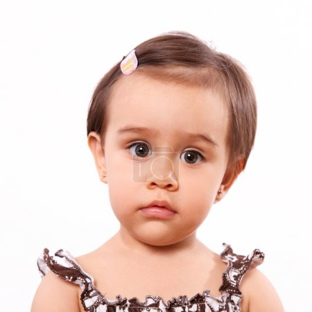 Photo pour Sérieux bébé fille regardant vers le bas sur fond blanc. gros plan - image libre de droit