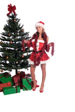 Photo pour Sexy Mme Père Noël près de l'arbre de Noël drapé dans une guirlande de mousseline - image libre de droit