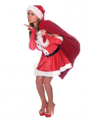 Photo pour Sexy Mlle Père Noël avec un sac de cadeaux sur son épaule et souffler un baiser - image libre de droit