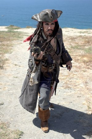 Photo pour Un capitaine pirate débarque et suit sa boussole, essayant de trouver le trésor enfoui. - image libre de droit