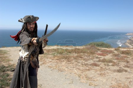 A Pirate Captain comes a shore and with his rapier and pistol drawn