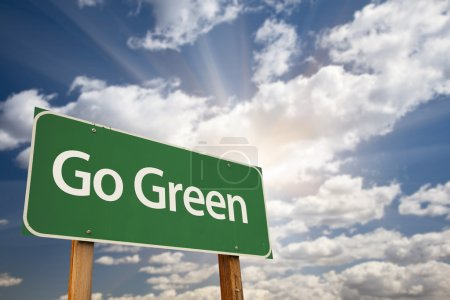 Foto de Go Green Road Sign Against Dramatic Clouds, Sky and Sun Rays. - Imagen libre de derechos
