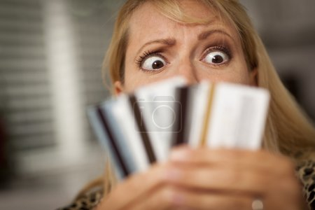 Photo for Upset Robed Woman Glaring At Her Many Credit Cards. - Royalty Free Image