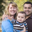 Happy Mixed Race Ethnic Family Posing for A Portra...