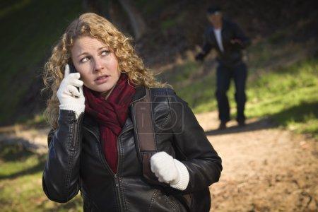 Photo pour Jolie jeune adolescente appelant sur téléphone portable avec mystérieux étrange homme se cachant derrière elle . - image libre de droit