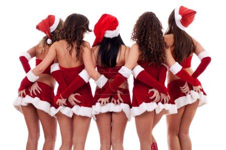 Photo pour Groupe de sexy jeunes femmes santa saisissant leurs culs sur fond blanc - image libre de droit