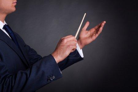 Photo pour Image recadrée d'un chef d'orchestre masculin dirigeant avec son bâton en concert - image libre de droit