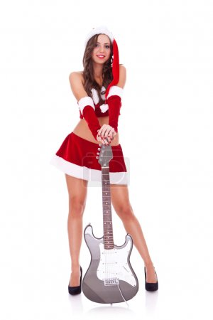 Photo for Sexy santa with great legs holding her electrig guitar on the ground, over white background - Royalty Free Image