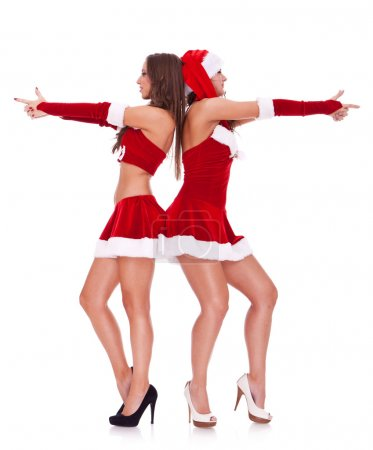 Photo for Side view of two sexy santa women posing as secret agents on white background - Royalty Free Image