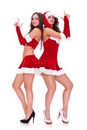 Photo for Back to back santa women, posing as secret agents, on white background - Royalty Free Image