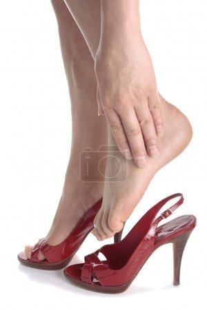 Woman legs wearing high heels massaging aching feet over white b