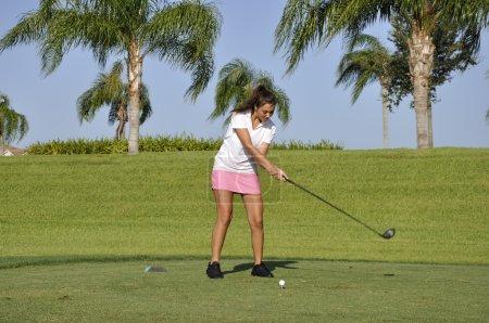 Photo pour Adolescente, prête à rouler une balle de golf sur un parcours de golf à naples, Floride - image libre de droit