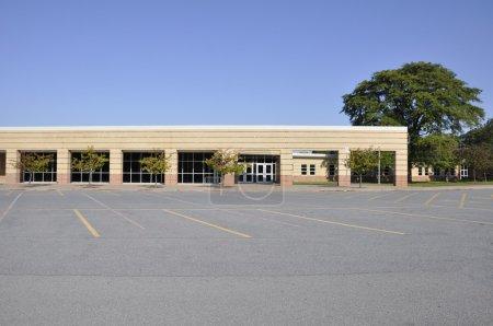 Photo pour Grand parking macadam vide près d'un bâtiment scolaire moderne - image libre de droit