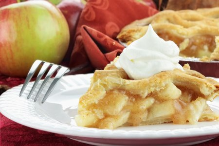 Slice of delicious fresh baked apple pie with whip...