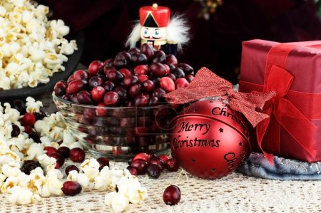 String of popcorn and cranberries with bowl of cra...