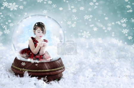 Photo for Little girl inside a snow globe blowing snow out of her hands. Copy space available. - Royalty Free Image