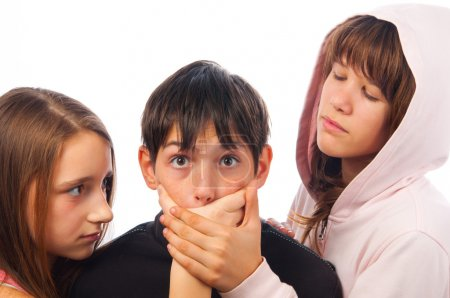 Two girls harrasing frightened boy