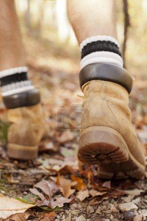 Photo pour Gros plan des bottes de randonnée de l'homme marchant sur un sentier à travers les bois en automne. - image libre de droit
