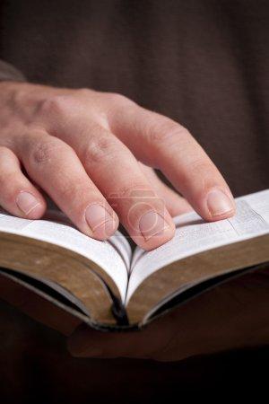 Photo pour L'homme tenant la Bible ouverte dans ses mains . - image libre de droit