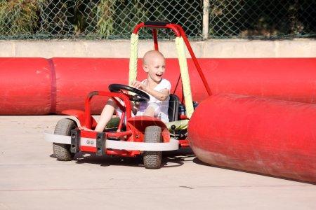 Photo pour Un caucasien enfant subissant un traitement de chimiothérapie en raison du cancer s'amuser sur un chariot d'aller à une fête foraine - image libre de droit