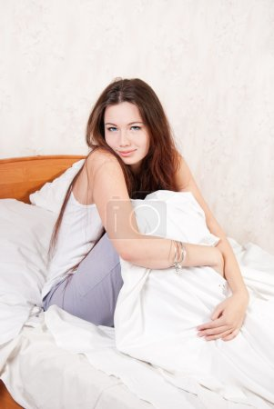A girl sitting on a bed