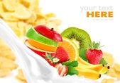 Milk splash with fruit mix on corn flakes background