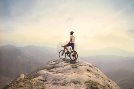 Photo for Cyclist standing on a peak over the mountains - Royalty Free Image