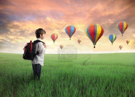 Foto de Niño en un prado verde con globos de aire caliente en el fondo - Imagen libre de derechos
