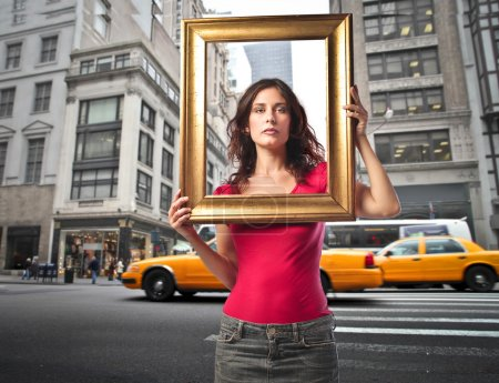 Photo for Young woman holding a frame with cityscape in the background - Royalty Free Image