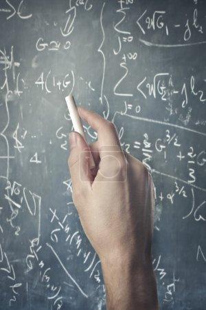 Photo pour La main de l'homme écrivant quelques calculs sur un tableau noir - image libre de droit