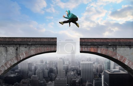 Photo for Young man jumping from one side of a broken bridge to the other - Royalty Free Image