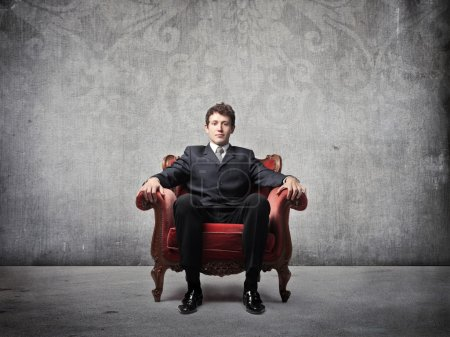 Businessman sitting on an armchair...